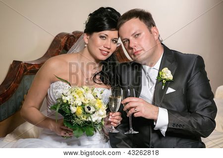 Portrait of the newlyweds on studio shooting with glasses of champagne