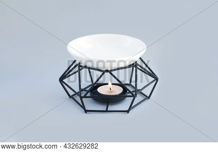 Modern Aroma Lamp Or Oil Burner With Burning Candle And Essential Oils. Aromatherapy Concept