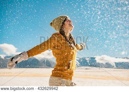 Young Happy Stylish Girl Whirls With Raised Hands And Enjoys The Snow In Mountains. Winter Holidays