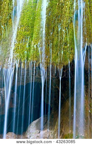 waterfall close-up with streams on green moos