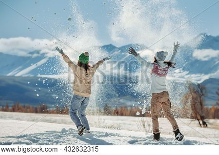 Two Happy Young Girls Are Having Fun And Tossing Snow In Mountains. Winter Holidays Concept