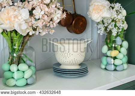 Enameled White Colander, Plates, Bouquet Of Flowers In Vase And Easter Eggs On Kitchen Table. Front