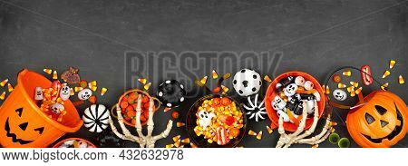 Halloween Trick Or Treat Bottom Border With Jack O Lantern Pails And Mixed Candy. Top View On A Blac