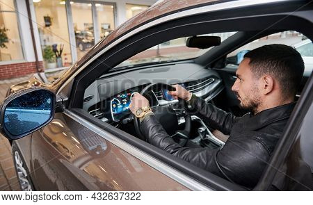 Close-up View Of Confident, Bearded Man Testing New Car In The Courtyard Of Car Dealership. Guy Putt