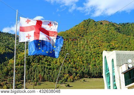 Georgian Flag With Eu Flag Waving Against The Early Autumn Hills Of Mestia Town, Svaneti Region, Geo