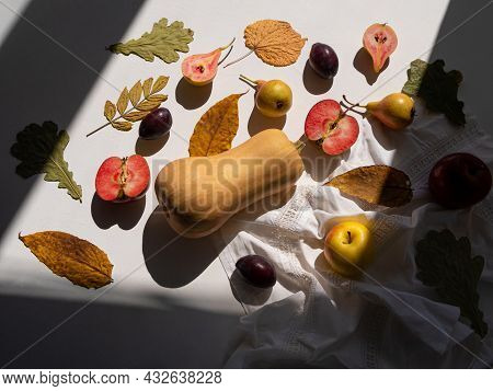 Autumn Flat Lay With Pumpkin Apples Pears Plums And Fall Leaves With Linen Table Cloth On White Back