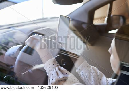 Young Multiracial Woman Texting And Driving Car. Woman Using Cellphone While Driving Car. Female Usi