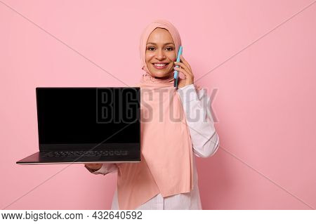 Attractive Successful Arab Muslim Woman In Pink Hijab Talks On Mobile Phone, Smiles With Toothy Smil