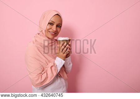 Arabic Muslim Pretty Woman With Covered Head In Pink Hijab Drinking Hot Drink, Tea Or Coffee From Di