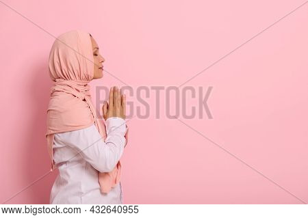 Side Portrait Of A Serene Arab Muslim Woman In Pink Hijab And Strict Outfit With Palms Folded Togeth