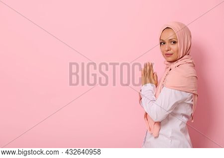 Muslim Arab Woman In Pink Hijab And Strict Outfit With Palms Folded Together At Chest Level Praying,