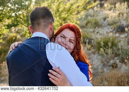 Gorgeous Happy Caucasian Plus Size Red Headed Woman Embracing Her Husband And Looking To A Camera. M