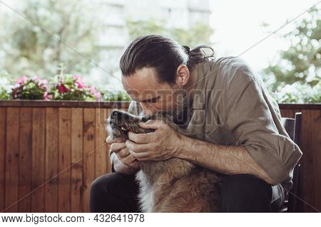 Adult Man Hugs His An Adult Man Hugs His Dog On The Balcony Of The House, Against The Backdrop Of Na