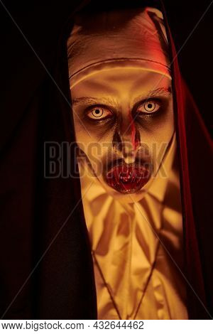 Close-up portrait of a devilish scary nun with bloody teeth standing in candlelight. Halloween and Horrors.