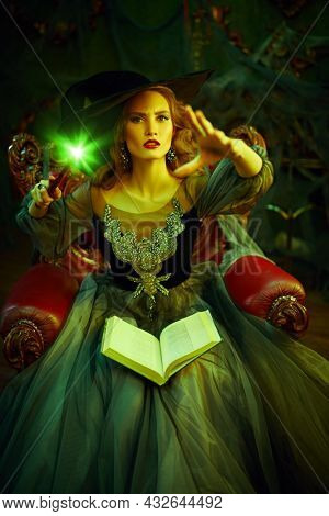 Portrait of a beautiful woman witch in a hat and beautiful dress sitting in an armchair with a book of spell in the old castle. Halloween. Celebration.