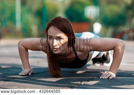 Purposeful Woman Does Push-ups. Sports Training, Active Lifestyle For The Thirties.