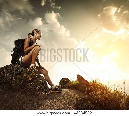 Young tourist with backpack relaxing on rock and enjoying sunset