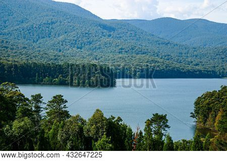 Hazy Green Woodland Hills Surrounding A Pristine Lake