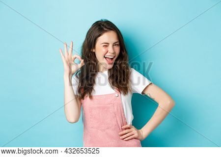 Image Of Cheerful Glamour Woman Winking And Showing Ok Sign To Recommend And Approve Nice Thing, Lik