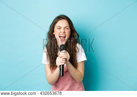 Excited Pretty Girl Singing Karaoke, Holding Microphone And Smiling Happy, Standing Over Blue Backgr