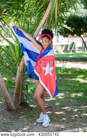 Latina Woman Wrapped In Cuban Flag Smiling At The Camera