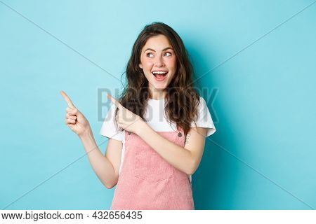 Portrait Of Happy Smiling Female Model With Glamour Blush, Pointing Fingers Left And Looking At Prom
