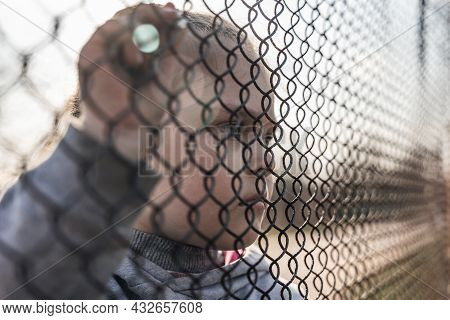 Little Girl With A Sad Look Behind A Metal Fence, Social Problems, Raising Children In Orphanages.