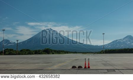 There Is A Marking On The Runway Of The Airfield. Majestic Conical Volcanoes With Snow-covered Slope