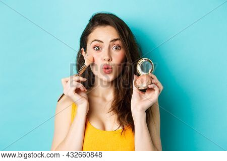 Beauty. Silly Glamour Girl Pucker Lips, Applying Make Up With Brush And Showing Blushes At Camera, S