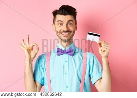 Shopping Concept. Smiling Handsome Male Shopper Showing Ok Sign And Plastic Credit Card, Buying Some