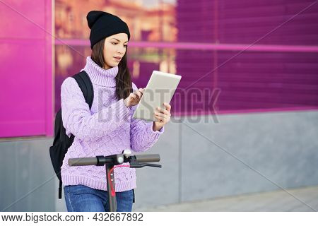 Woman In Her Twenties With Electric Scooter Using Digital Tablet Outdoors.