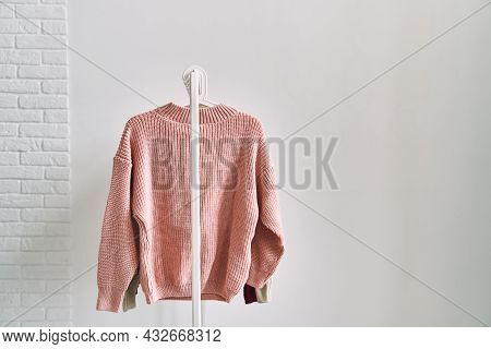 A Woolen Sweater Hanging On A Hanger On A White Background. Warm Clothes Sale.