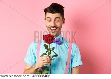 Valentines Day And Romance Concept. Happy Boyfriend Looking At Red Rose While Waiting For Lover In B