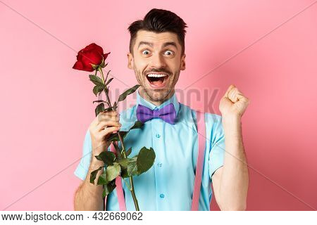 Valentines Day And Romance Concept. Excited Boyfriend Jumping From Happiness On Romantic Date, Holdi