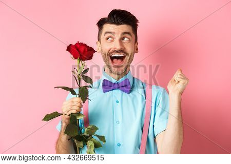 Romance And Valentines Day Concept. Cheerful Man In Bow-tie Screaming From Happiness, Holding Red Ro