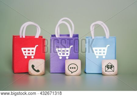 Contact Method Icon On Wooden Cube And Blurred Small Shopping Bag With Shopping Cart Icon On Green B