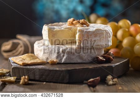Organic Homemade Camembert Or Brie Cheese On A Wooden Board With Grapes And Nuts And Honey. Rustic S
