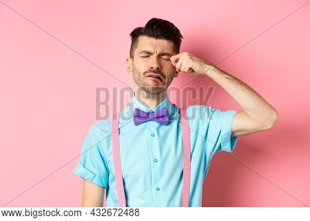 Image Of Heartbroken Guy Crying And Wiping Tear Off Face, Sobbing And Feeling Sad Or Lonely, Standin
