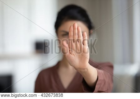 Courageous Young Female Extend Hand In Stop Gesture Saying No