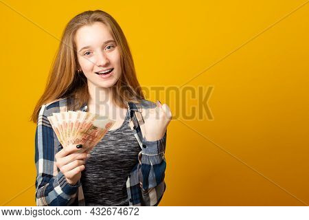 Banner. Happy Beautiful Young Woman Holding Rubles Money Isolated Yellow Background. Sale, Finance,