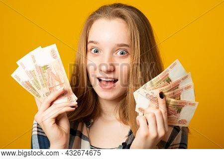 Happy Beautiful Young Woman Holding Rubles Money Isolated Yellow Background. Sale, Finance, Banking,