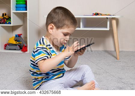 A Small Child And A Mobile Phone In The Childrens Room With Place For Text. Cartoons And Dependence