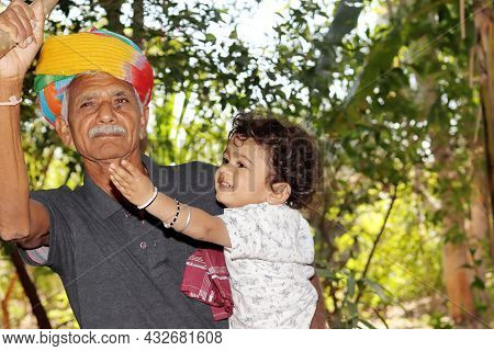 Close-up Portrait Of A Small Indian Son To Asian Elderly Grandfather Looks Up At The Fruit In The Ga