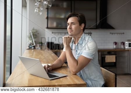 Dreamy Male Work On Computer Look In Distance