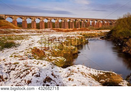 Long Exposure Of The Big Water Of Fleet Surrounded By Snow In Winter, With The Railway Viaduct In Th