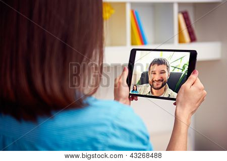 man and woman communicating through video chat on tablet pc