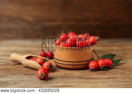 Ripe Rose Hip Berries With Green Leaves And Scoop On Wooden Table