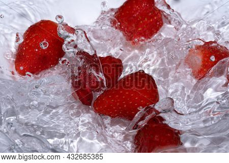Ripe Sweet Fresh Strawberry Is Washed In Clean Cold Water With Splashes And Bubbles Close-up