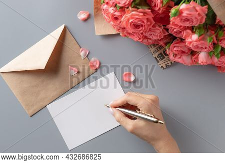 Woman Writing Greeting Card On Gray Table With Bouquet Of Pink Roses. Greeting Card For Valentine's