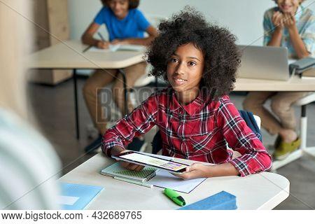 Happy African American Schoolgirl Looking Listening To Teacher Using Tablet Device Sitting In Classr